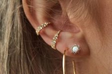 05 embellished ear cuffs, a stud earring and a large gold hoop with a rhinestone on it for a bold look