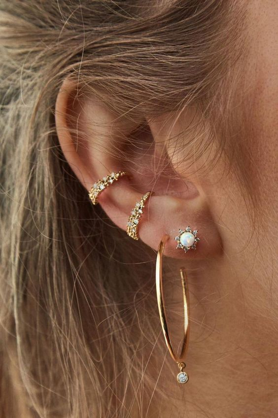 embellished ear cuffs, a stud earring and a large gold hoop with a rhinestone on it for a bold look