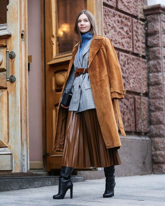 a layered look with a blue top, a grey blazer, a rust colored trench, a brown leather midi and black boots