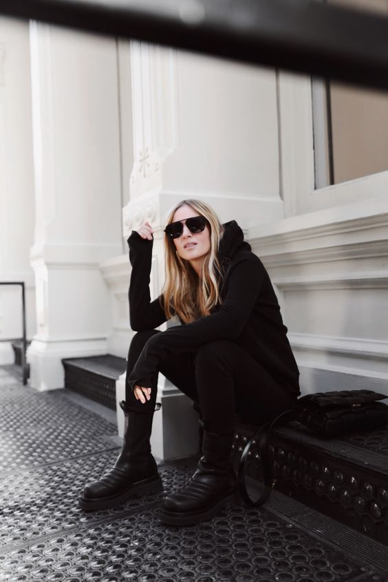 a total black look with a black hoodie, black jeans, black chunky boots and a bag for every day