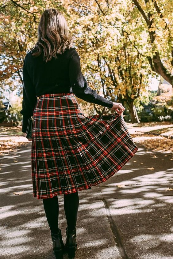 a black turtleneck, a plaid pleated midi skirt, black tights and black booties for fall or winter