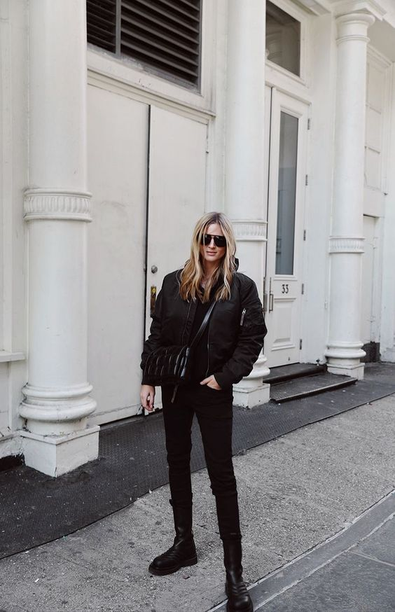 a total black look with a hoodie, jeans, chunky boots, a puff jacket and a black snakeskin bag