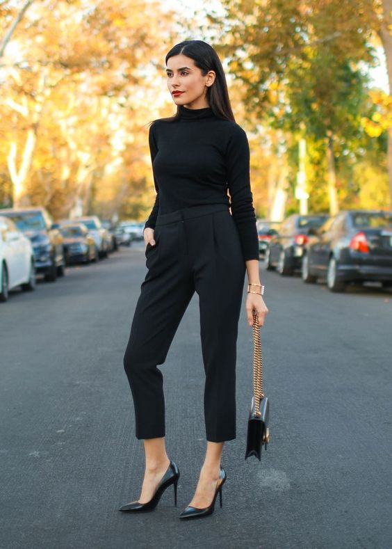 a black turtleneck and cropped pants, black heels and a bag on gold chains plus a red lip for a bold touch