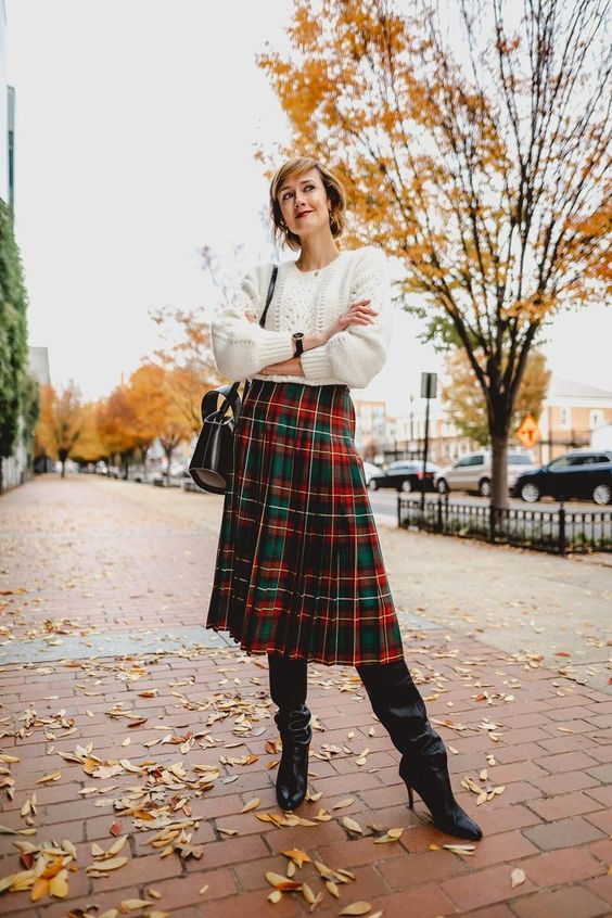 a classic Christmas look with a white sweater, a bright tartan pleated midi and black boots