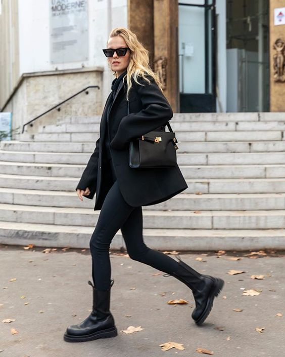 a total black outfit with a hoodie, skinnies, chunky boots, a short coat and a black bag