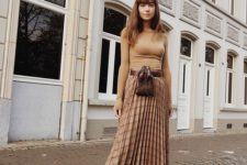 09 a chic look with a nude fitting top, a plaid pleated midi skirt and black boots plus a waist bag