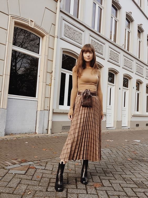 a chic look with a nude fitting top, a plaid pleated midi skirt and black boots plus a waist bag