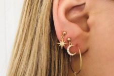 09 three gold earrings including a hoop with an embellished star, a star and a half moon earring for a cool look
