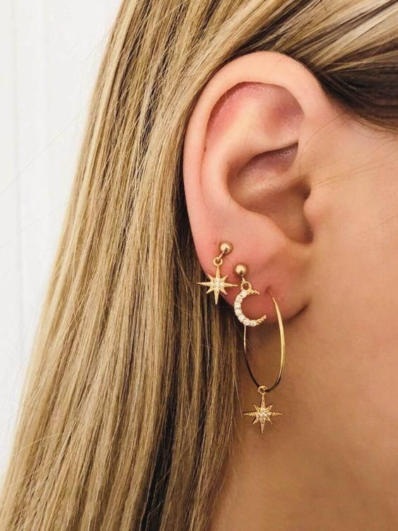 three gold earrings including a hoop with an embellished star, a star and a half moon earring for a cool look