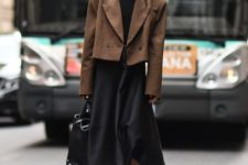 10 a black midi A-line dress, an oversized cropped brown jacket, a black bag and chunky boots