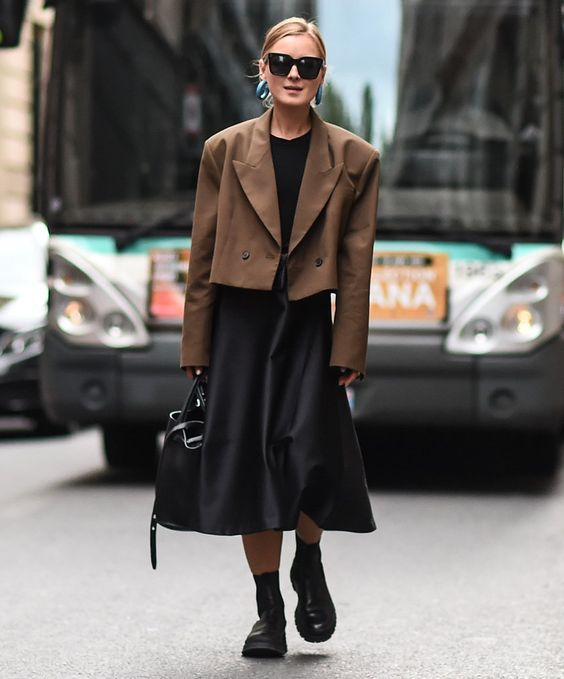 a black midi A-line dress, an oversized cropped brown jacket, a black bag and chunky boots