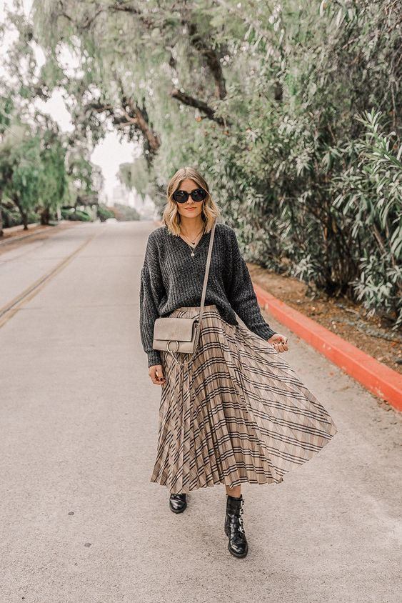 a comfy look with an oversized grey sweater, a neutral pleated plaid midi, black boots and a grey bag