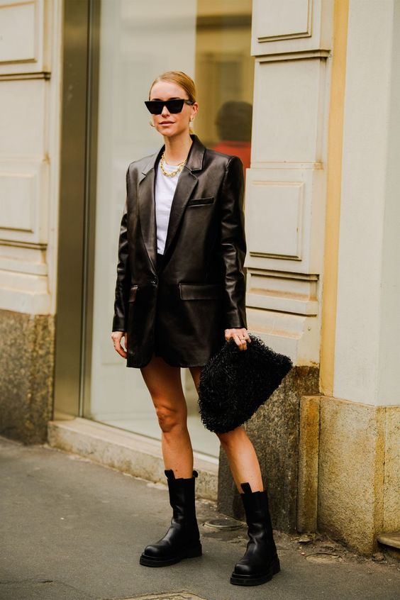 a quirky look with a white tee, a black mini, an oversized black leather jacket, a fluffy clutch and chunky boots