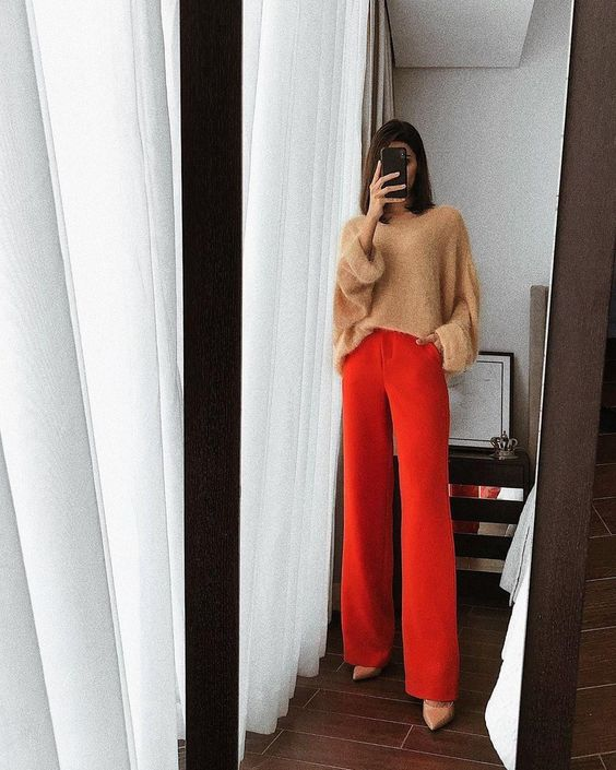 a tan oversized sweater, red palazzo pants and tan shoes for a minimal yet bright look