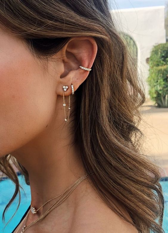 an embellished ear cuff and a matching earring plus a chain one make the look super chic and bold