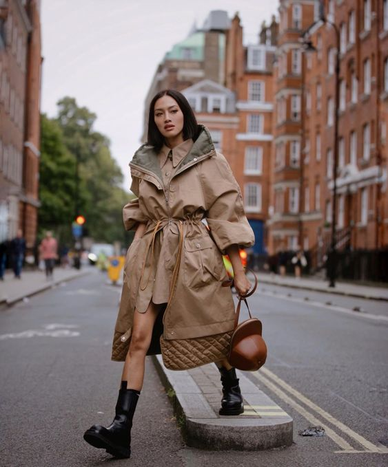 a tan colored shirtdress, a matching grey and tan parka, black chunky boots and a quirky brown bag