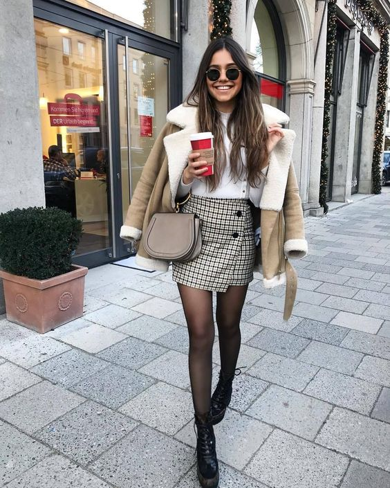 a white top, a tweed mini skirt with buttons, a neutral shearling coat, a tan bag on a ring, black boots