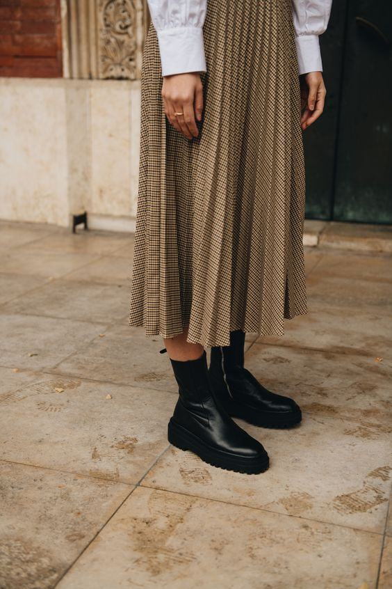 a vintage-infused look with a plaid pleated midi, a white shirt and black chunky boots