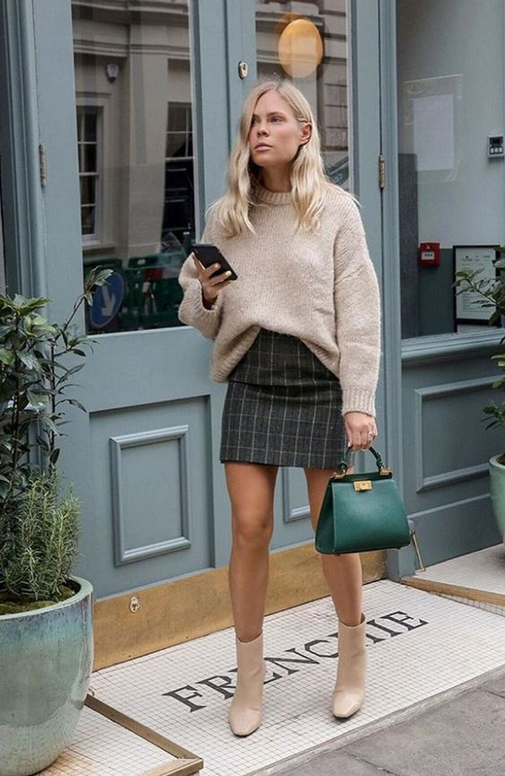 a neutral sweater, a grey plaid mini skirt, tan boots and an emerald bag for fall or winter