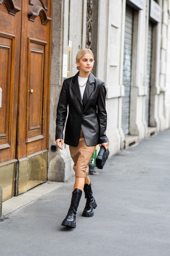 an edgy look with a white tee, a black leather jacket, a tan leather midi, chunky boots and a black clutch