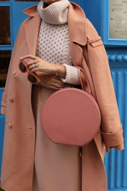 With beige sweater, coat and pale pink skirt