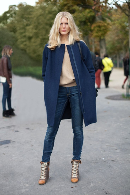 With beige sweatshirt, jeans, black bag and lace up ankle boots