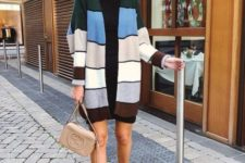 With black mini dress, beige sock boots and beige leather small bag