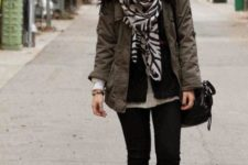 With black pants, brown lace up boots, parka coat and bag