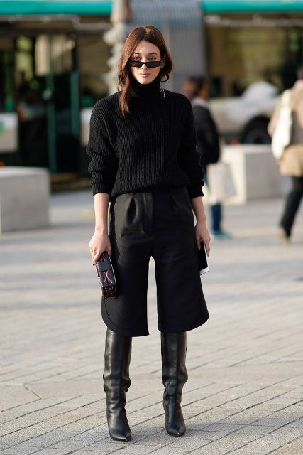 With black sweater, clutch and black culottes