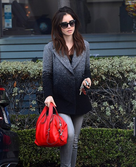 With black t shirt, gray jeans and red bag