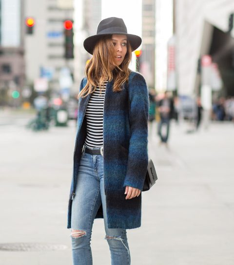 With black wide brim hat, striped shirt, distressed jeans and bag