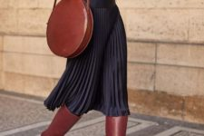 With blouse, pleated midi skirt and brown high boots