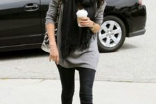 With gray long sweater, black pants, black fringe scarf and printed bag