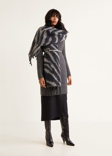 With gray long sweater, embellished belt, black midi skirt and black high boots