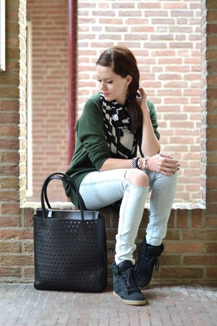 With green shirt, distressed jeans, black tote bag and lace up boots