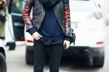 With navy blue sweater, black pants, black and red leather jacket, hat and gray socks