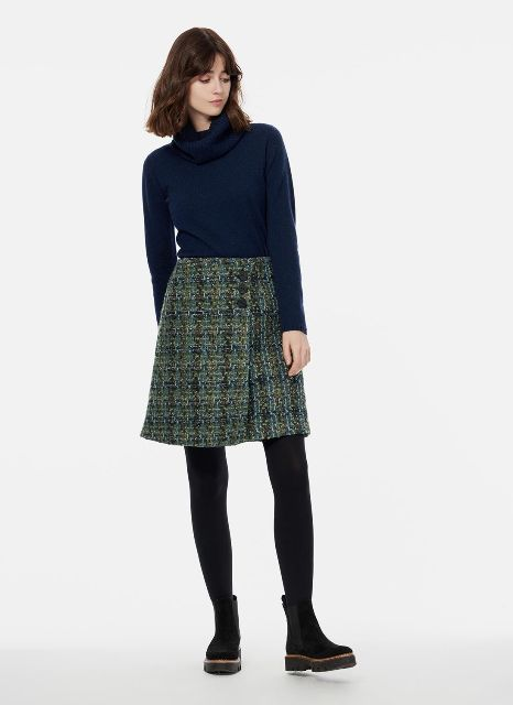 With navy blue sweater, black tights and black flat boots
