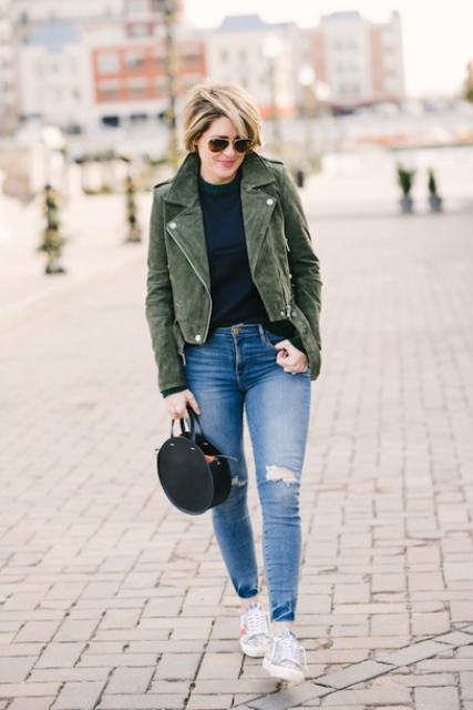 With navy blue sweater, distressed jeans, printed sneakers and olive green suede jacket