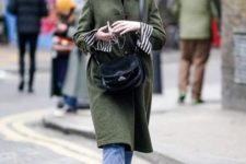 With olive green coat, cropped jeans, striped shirt and black crossbody bag