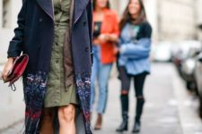 With olive green dress, navy blue coat, brown scarf and clutch