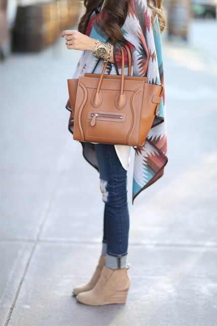 With printed poncho, brown leather bag and cuffed jeans