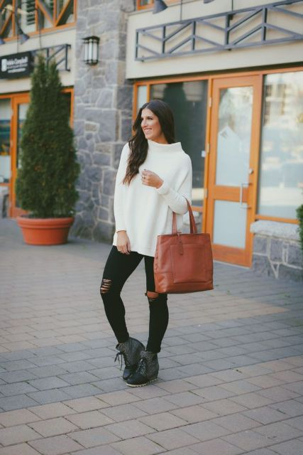 With white loose sweater, brown tote bag and distressed pants