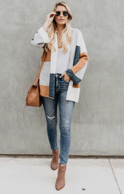 With white t shirt, distressed skinny jeans, brown bag and ankle boots