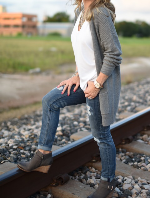 With white t shirt, gray cardigan and distressed jeans