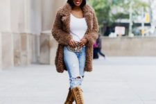 With white top, distressed jeans, black cap, fur coat and printed bag