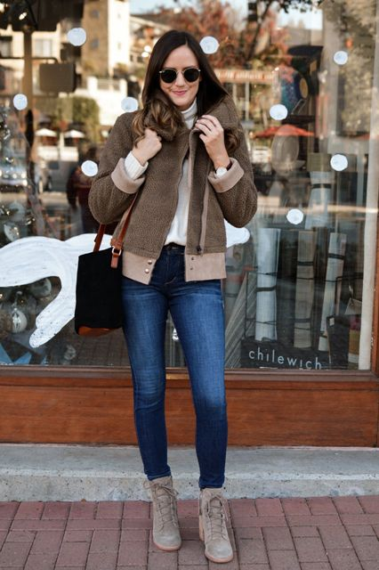 With white turtleneck, fur jacket, skinny jeans and black and brown bag