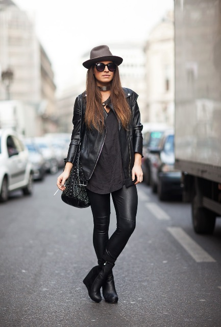 With wide brim hat, loose shirt, black leather jacket, embellished bag and leather pants