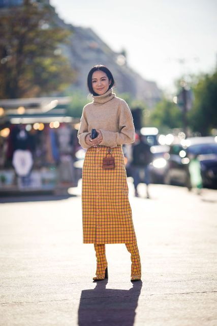 With yellow and black checked midi skirt, checked high boots and mini bag