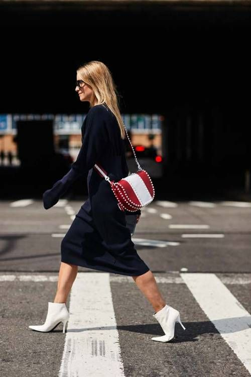 a black midi sweater dress, white heeled booties and a red and white striped saddle bag