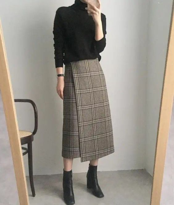 a black oversized turtleneck, a tweed wrap midi skirt, black booties for a stylish and casual look